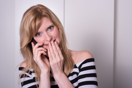 strictly: beautiful blonde woman is very upset during a phone call Stock Photo