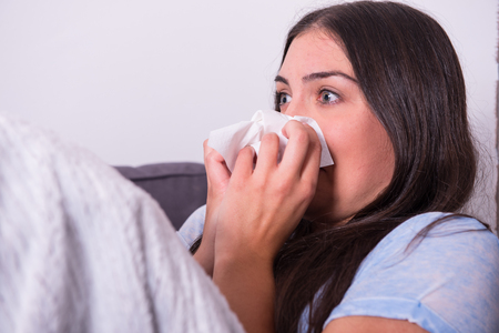 woman on couch: Young woman lying ill on the couch at home