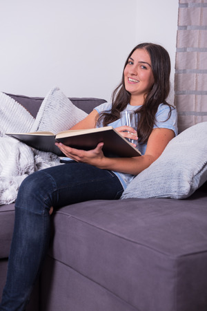 woman on couch: Young woman reading home on the couch in a book Stock Photo