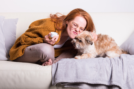 Beautiful, red-haired woman with orange sweater sits with her dog