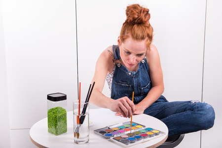 atttractive redhead is painting with water colours