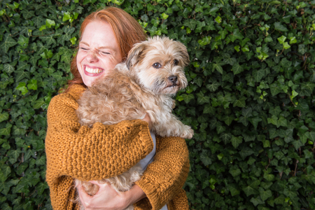 Beautiful red-haired woman has her little dog in her arms Stock Photo