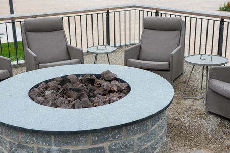 Round gas fire station with basalt stones with tables and lounges Stock Photo