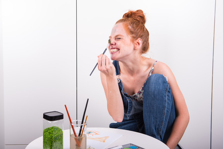 attractive redhead is making fun during painting with water colours at home