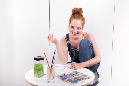 attractive redhead is painting with water colours at home