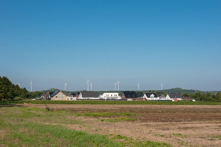 Wind turbines behind a new building settlement in rural surroundings Stock Photo