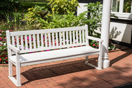 Place to rest - white lacquered wooden bench in the garden Stock Photo