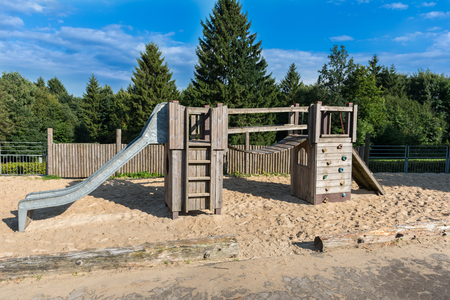 Childrens playground with climbing frame on the edge of the forest in front of a blue sky Stock Photo