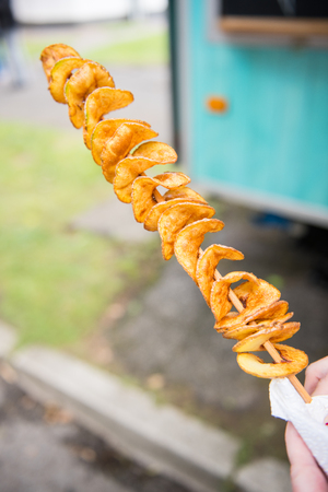 Street Food - salted potatoes grilled on a wooden skewer