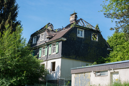 Burned out house with dilapidated roof structure with charred roof beams