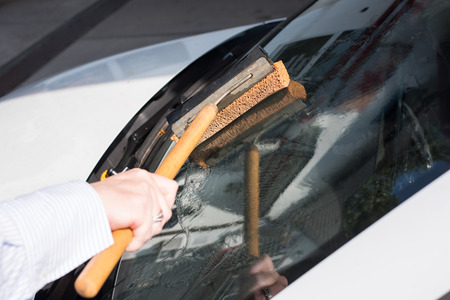 Woman cleans the windshield of her car Stock fotó