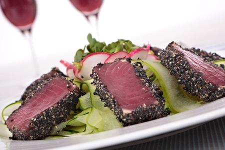 atun: Atún de aleta amarilla braseado recubierto con semillas de sésamo y ensalada verde en un plato blanco. Copas de vino tinto fuera de foco en el fondo.