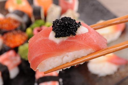 Tuna sushi with caviar held by chopsticks from background of assorted sushi platter