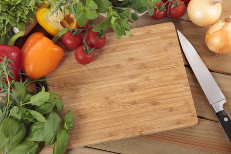 chopping: Herbs and vegetables with a blank chopping board. Space for copy.