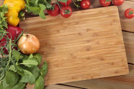 kitchen knife: Hierbas y verduras con una tabla de cortar en blanco. Espacio para la copia.