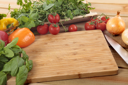 Herbs and vegetables with a blank chopping board. Space for copy.