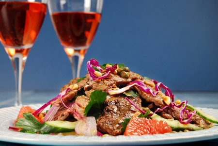 barbecued: Barbecued beef steak salad with dressing and glasses of wine Stock Photo