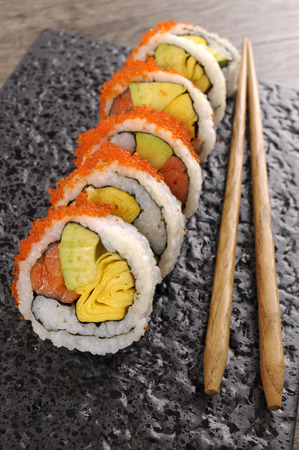egg roll: California roll sushi with caviar and chopsticks on a black plate