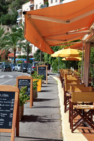 villefranche sur mer: Typical French restaurant scene of tables and chairs and menu board Stock Photo