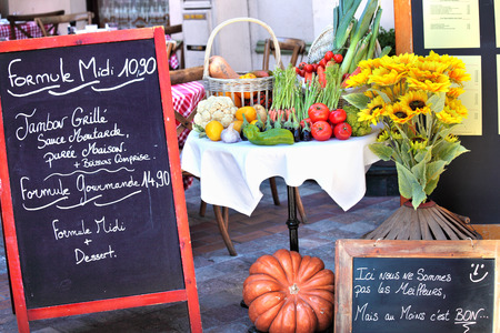 Menu board with arrangement of vegetables and sunflower at French restaurant