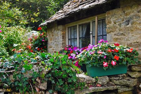 Stenen muur met bloemen van landelijk huisje in Cotswolds, Engeland