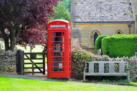 Telefooncel en bank in het Engels landschap van Cotswolds Stockfoto