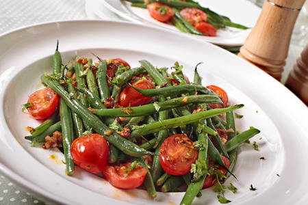 french bean: Green beans and tomato salad on white plate Stock Photo