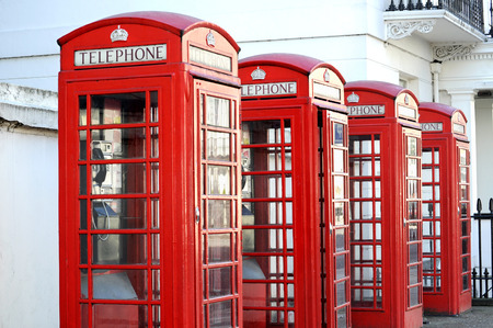english famous: Row of red telephone boxes in London street