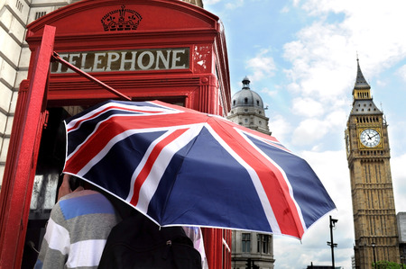 Tourist with British umbrella in telephone box and Big Ben in London