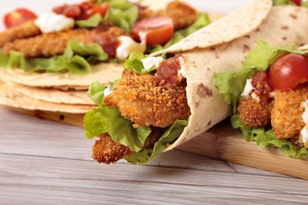 Making deep fried chicken fajita wrap sandwich with stack of tortillas
