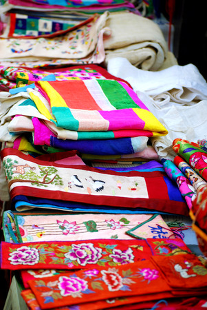 Cloths of embroidered silk and linen in Asian market photo