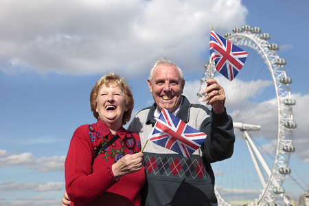 Senior couple holding British flag in London with Millenium wheel in the background Imagens