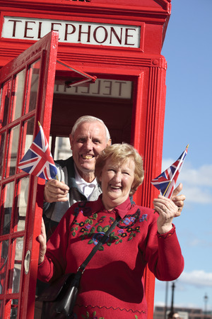 telephone box: Senior couple with red telephone box holding British flag in London