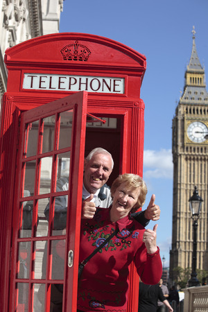 telephone box: Senior couple with red telephone  box in London. Big Ben in the background. Stock Photo