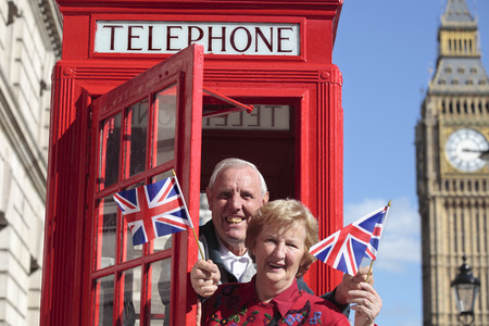 telephone box: Senior couple with red telephone box holding British flag in London. Big Ben in the background. Stock Photo