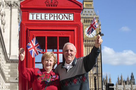 jack in a box: Senior couple with red telephone box holding British flag in London. Big Ben in the background. Stock Photo