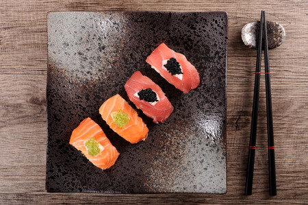 sushi plate: Tuna and salmon sushi set with caviar and chopsticks. Top view.