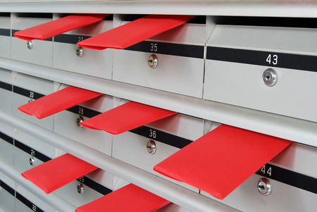 Letterboxes in rows with letters in red envelopes