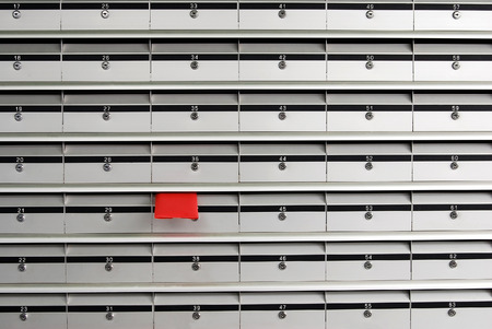 red envelope: Letterboxes in rows with letter in red envelope Stock Photo