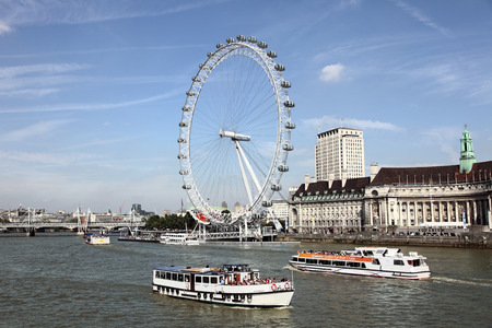 london eye: London, England - September 2, 2011: Landscape of the River Thames in London dominated by the London Eye Ferris wheel. Picture include tourist boats giving some indication of the huge size of the London Eye.