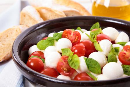 caprese salad: Caprese salad with mozzarella, cherry tomatoes and basil leaves
