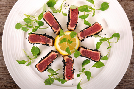 salade verte: Seared tuna coated sesame seeds with green salad on white plate. Top view. Banque d'images