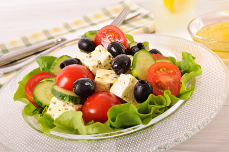 Greek salad in glass bowl with sauce photo