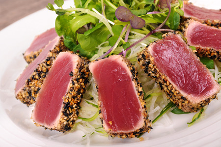 seafood salad: Seared tuna coated sesame seeds with green salad on white plate Stock Photo