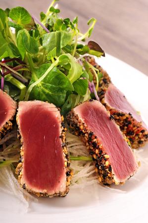 seared: Seared tuna coated sesame seeds with green salad on white plate Stock Photo