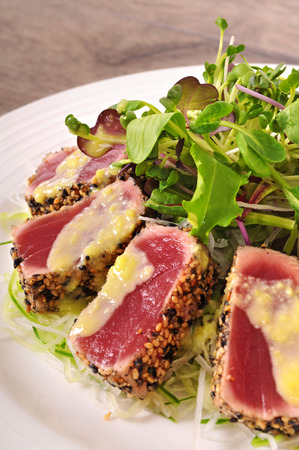 ahi: Seared tuna coated sesame seeds with sauce and green salad on white plate