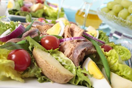 potato tuna: Nicoise salad closeup with grapes and wine glass on the background