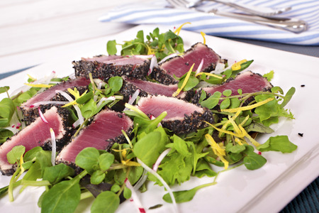ahi: Seared Ahi tuna coated with sesame seeds and green salad on white plate. Stock Photo