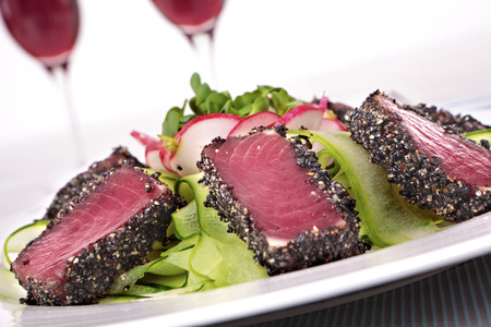 Seared tuna coated sesame seeds with green salad on white plate Imagens