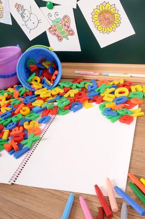 verticales: Cartas plásticas del alfabeto en el escritorio de la escuela
